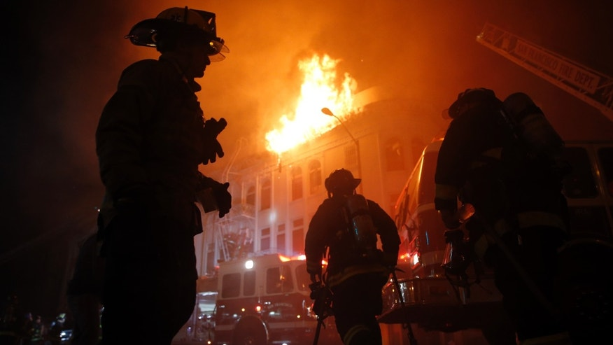 Jan. 28, 2015: San Francisco Fire Department members fight a four-alarm fire at 22nd and Mission Street in San Francisco, Calif.,