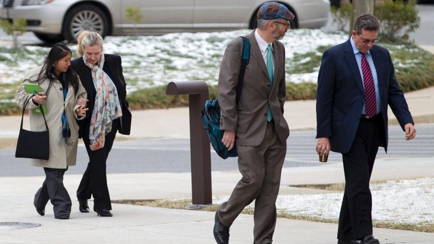 Sandra Dunham, second from left, and her husband Paul Dunham, right arrives at U.S. District Court in Greenbelt, Md., Thursday, Jan. 29, 2015, for her sentencing. Paul Dunham, who was president of Pace USA, and his wife Sandra Dunham, who was the director of sales and marketing, were extradited from England to the U.S. to face charges of conspiracy, wire fraud and money laundering. (AP Photo/Jose Luis Magana)