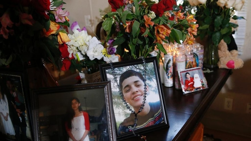 A rosary is draped over a portrait of 17-year-old Jessica Hernandez in her Thornton, Colo., home on Wednesday, Jan. 28, 2015. The teenager was killed after she allegedly hit and injured a Denver Police Department officer while driving a stolen vehicle early Monday in northeast Denver alleyway. (AP Photo/David Zalubowski)