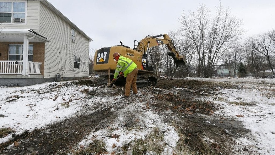 In a photo from, Thursday, Jan. 22, 2015, a crew from Adamo Demolition preps the site of a former vacant home for backfill in southwest Detroit. The actual number of Detroit squatters is unknown, but a real estate agent told the AP that about 30 percent of more than 100 empty homes she has shown to prospective buyers have had evidence that someone was _ or recently had been _ living inside. (AP Photo/Carlos Osorio)