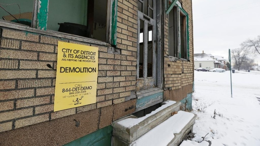 In a photo from, Thursday, Jan. 22, 2015, a demolition sign is posted on a vacant house in southwest Detroit. The actual number of Detroit squatters is unknown, but a real estate agent told the AP that about 30 percent of more than 100 empty homes she has shown to prospective buyers have had evidence that someone was _ or recently had been _ living inside. (AP Photo/Carlos Osorio)