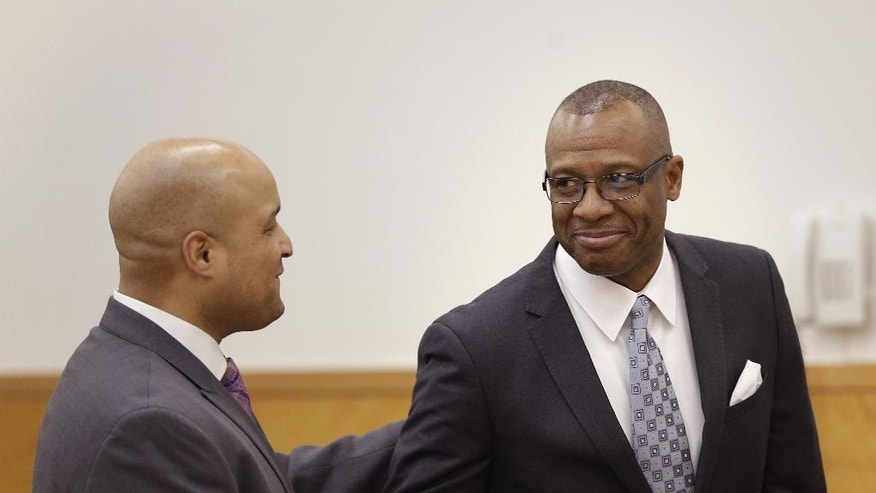 Michael Waithe, right, is congratulated by his attorney, Matthew Smalls, after being exonerated in New York, Thursday, Jan. 29, 2015.  A state Supreme Court judge granted a prosecutor's motion to vacate Waithe's 1987 burglary conviction.   Brooklyn District Attorney Ken Thompson says in a statement Waithe came to the U.S. seeking a better life but was instead framed for a crime he didn't commit. The green card-holder faces deportation based on the conviction. (AP Photo/Seth Wenig)