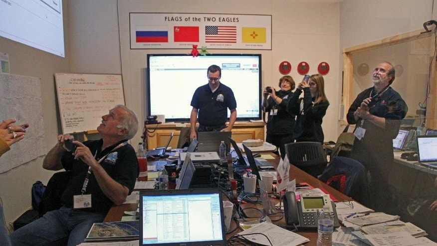 Members of the Two Eagles balloon mission control team watch a giant screen in Albuquerque, N.M., as pilots Troy Bradley and Leonid Tiukhtyaev surpass a gas ballooning distance record on Thursday, Jan. 29, 2015. Bradley and Tiukhtyaev were crossing over the Pacific Ocean as part of their record breaking challenge. (AP Photo/Susan Montoya Bryan)
