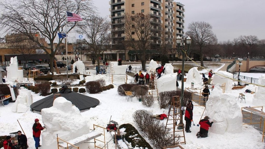 CORRECTS SPELLING OF LAKE GENEVA - In this photo taken Jan. 29, 2015 in Lake Geneva Wis., artists from 10 states take part in the U.S. National Snow Sculpting Championship. They started sculpting the nine-foot high blocks of snow on Wednesday and judging is set for Saturday. (AP Photo/Carrie Antlfinger)