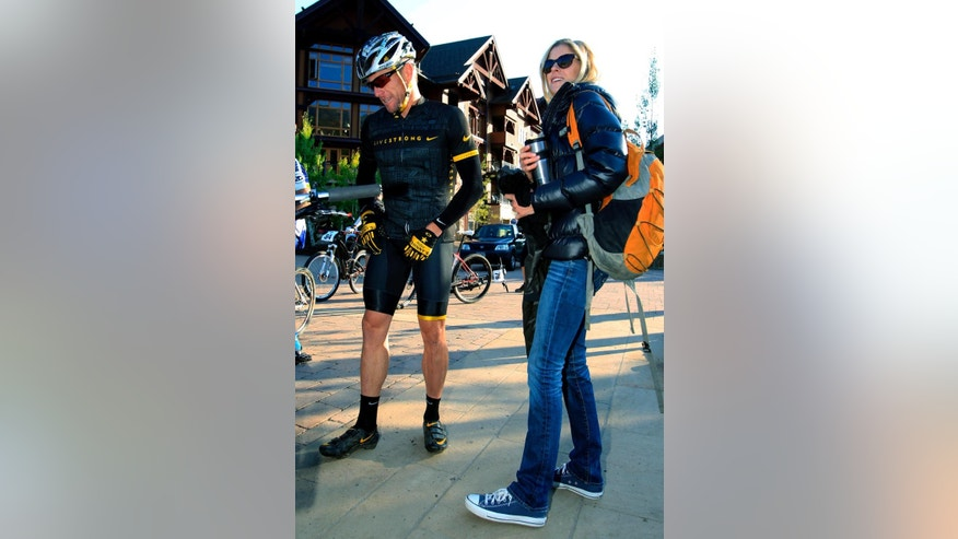 FILE - In this Aug. 25, 2012, file photo, Lance Armstrong, left, prepares to take part in the Power of Four mountain bicycle race, as his girlfriend Anna Hansen looks on, in Snowmass Village, Colo. Authorities say the disgraced cyclist hit two parked cars after a night of partying in Aspen but agreed to let his girlfriend take the blame to avoid national attention. Police say they cited Armstrong after the Dec. 28, 2014, hit-and-run but only after his girlfriend, Anna Hansen, admitted to lying for him.  (AP Photo/David Zalubowski, File)