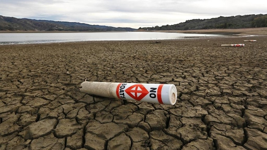FILE - In this Feb. 4 2014 file photo, a warning buoy sits on the dry, cracked bed of Lake Mendocino near Ukiah, Calif.  State officials reported Tuesday, Feb. 3, 2015, that residents in drought-stricken California met Gov. Jerry Brown's call to slash water use by 20 percent for the first time in December, when water use fell by 22 percent compared to the same month in 2013. (AP Photo/Rich Pedroncelli, File)