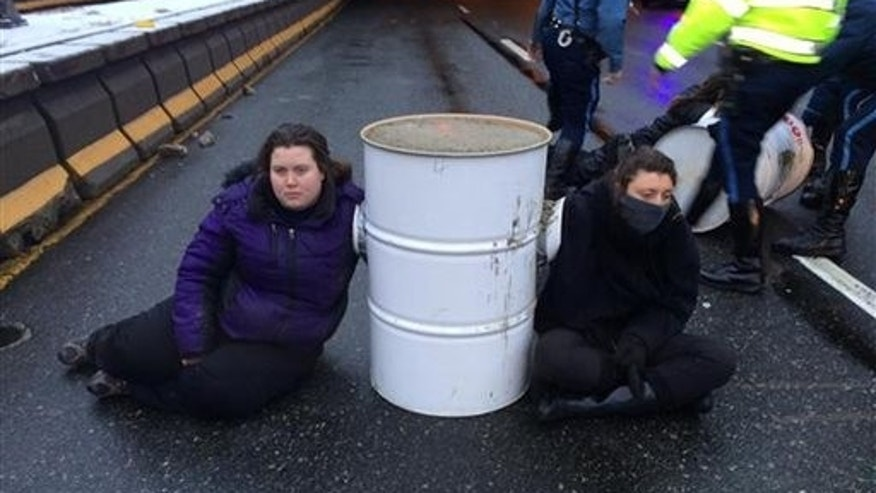 Protesters from the Boston contingent of Black Lives Matter sit near a barrel on Interstate 93 in Milton, Mass., on Jan. 15, 2015. (AP Photo/Massachusetts State Police)