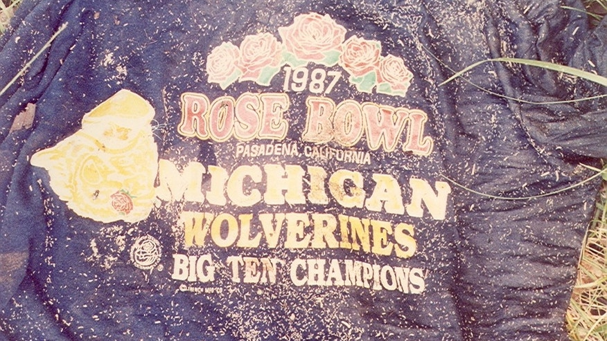 "The victim was found wearing this dark blue, short sleeve ""1987 Rose Bowl"" t-shirt, size 1XL."
