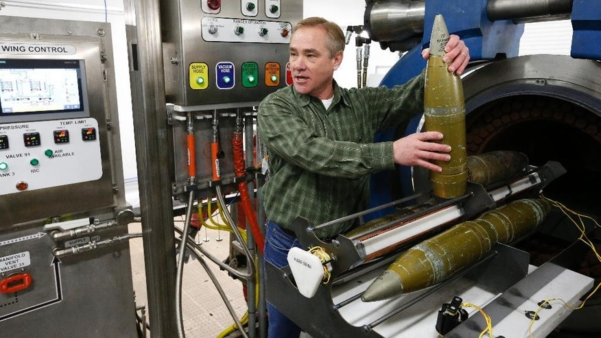 In this Jan. 29, 2015 photo, project manager Steve Bird holds an inert 105mm shell as he demonstrates the use of the explosive destruction system used for destruction of leaky or otherwise problematic chemical munitions, inside the Pueblo Chemical Depot, east of Pueblo, in southern Colorado. The United States is about to begin destroying its largest remaining stockpile of chemical-laden artillery shells, a milestone in the global campaign to eradicate a debilitating weapon that still creeps into modern wars. (AP Photo/Brennan Linsley)