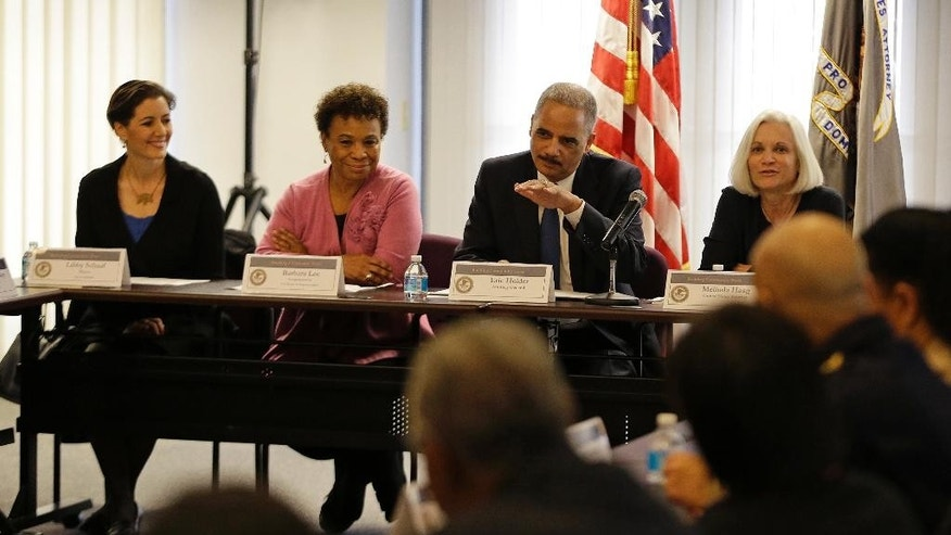 Attorney General Eric Holder gestures while speaking during a building community trust roundtable discussion with law enforcement, elected officials and community leaders Thursday, Feb. 5, 2015, in Oakland, Calif. Sitting alongside Holder from left are Oakland Mayor Libby Schaaf, Congresswoman Barbara Lee and U.S. Attorney Melinda Haag. Holder talked about law enforcement and community relations in Oakland, a city that experienced violent demonstrators against police abuse last year. Oakland is the sixth and last city the attorney general has conducted these police-community relations since unarmed black men were killed by police in Ferguson, Missouri and New York. (AP Photo/Eric Risberg)