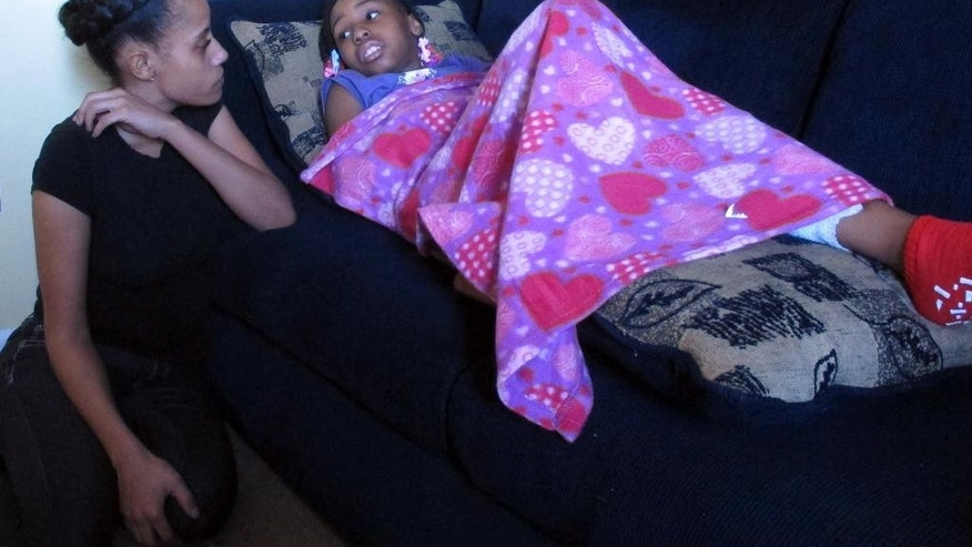 Shanita Miller sits in her Indianapolis apartment on Thursday, Feb. 5, 2015, next to her 9-year-old daughter, Sinai, resting on a living room couch. The third-grader was shot in the leg Tuesday afternoon as she was about to head to a weekly Girl Scouts meeting to pick up boxes of Girl Scout cookies to sell door-to-door for the second straight year. Although she's now healing, the youngster is still racking up sales thanks to an online cookie drive organized by the Girls Scouts of Central Indiana. Proceeds from that drive will help send Sinai and her troop on a trip. (AP Photo/Rick Callahan)