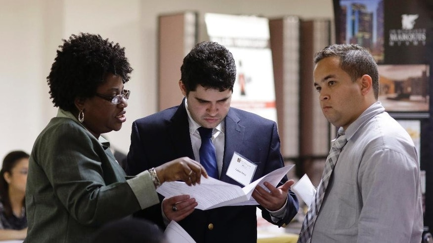 In this Friday, Jan. 23, 2015 photo, instructor Lavinda Young, left, helps Fabian Perez, center, and Lazaro Chaviano, right, with their resumes during a job fair at the Hospitality Institute, in Miami. The U.S. Labor Department reports on the number of people who applied for unemployment benefits for the week ending Jan. 24 on Thursday, Feb. 5, 2015. (AP Photo/Lynne Sladky)
