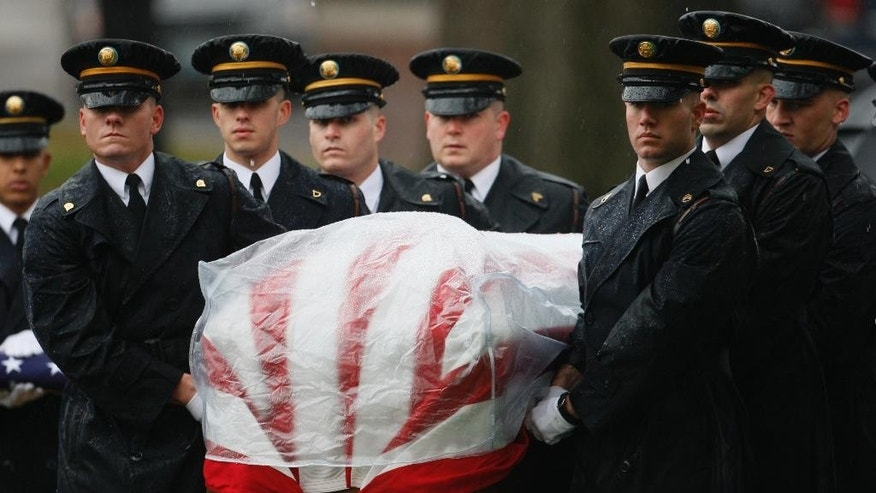 FILE - In this Nov. 23, 2009 file photo. the honor guard carries the casket of  Fort Hood shooting victim Army Lt. Col. Juanita Warman at her burial services at Arlington National Cemetery. The Army said in a letter addressed to Congress on Friday, Feb. 6, 2015 that the victims of the 2009 shooting that left 13 dead and more than 30 wounded will receive the Purple Hearts many have said they deserve. (AP Photo/Charles Dharapak, File)