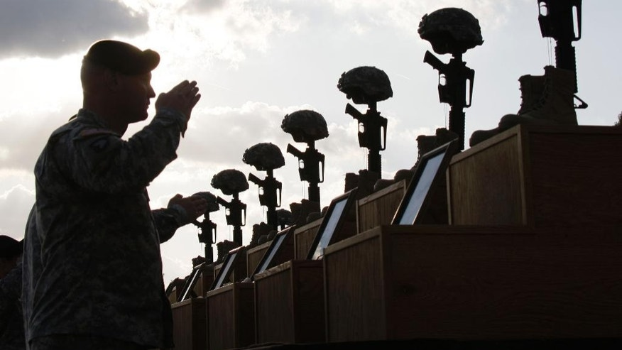FILE- In this Nov. 10, 2009 file photo, soldiers salute as they honor victims of the Fort Hood shooting at a memorial service at Fort Hood, Texas. The Army said in a letter addressed to Congress on Friday, Feb. 6, 2015 that the victims of the 2009 shooting that left 13 dead and more than 30 wounded will receive the Purple Hearts many have said they deserve. (AP Photo/Donna McWilliam, File)