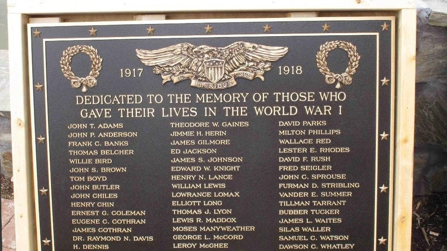 In this Jan. 22, 2015 photo shows one of the plaques that Greenwood Mayor Welborn Adams would like to replace on the Greenwood County's memorial in Greenwood, S.C. The memorial honors its citizens who died in recent wars. The World War I and World War II soldiers on the original plaques are separated into colored and white, and Adams wants to put new plaques on the statue, but a state law won't allow it. (AP Photo/Jeffrey Collins)