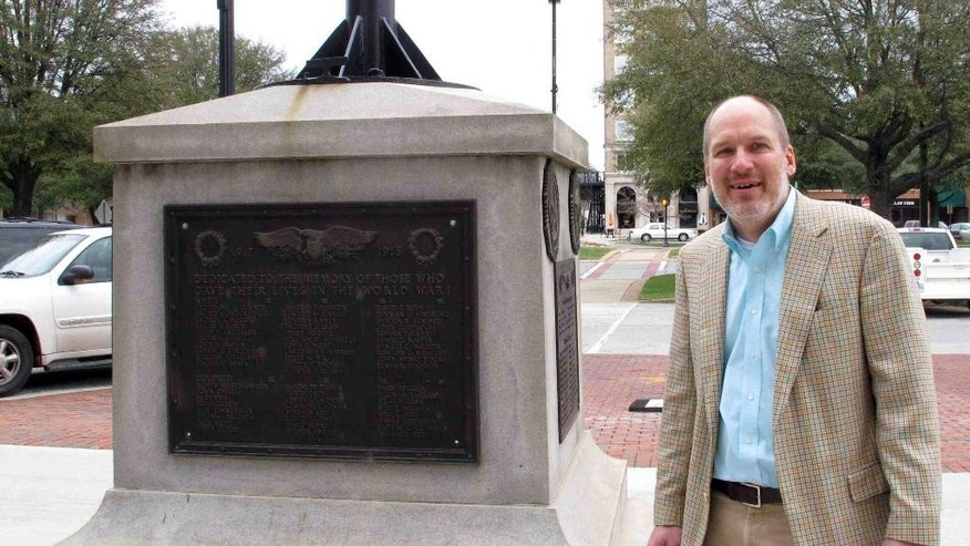In this Jan. 22, 2015 photo, Greenwood Mayor Welborn Adams stands beside the Greenwood County memorial in Greenwood, S.C.,  that honors its citizens who died in recent wars. The World War I and World War II soldiers are separated into colored and white. Adams raised $15,000 to put new plaques on the statue, but a state law won't allow him to put them up. (AP Photo/Jeffrey Collins)