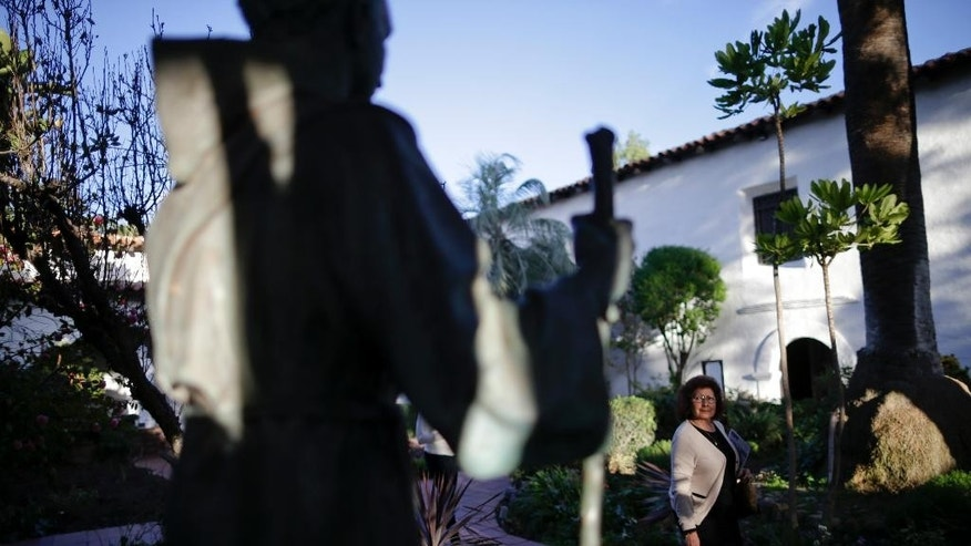 In this Jan. 27, 2015 image, a woman passes a statue of Franciscan missionary Junipero Serra at the Mission San Diego de Acala in San Diego. Pope Francis' announcement that he will canonize Serra is meeting resistance by some in California and beyond, as critics say he wiped out native populations, enslaved converts and spread disease. (AP Photo/Gregory Bull)