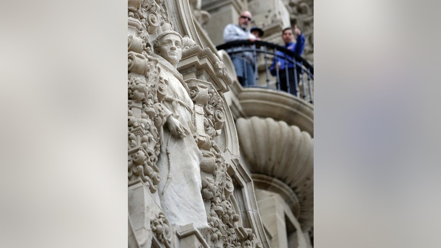In this Jan. 30, 2015 image, people look down from a balcony as a sculpture of Franciscan missionary Junipero Serra looks out from a facade on the California Tower at Balboa Park in San Diego. Pope Francis' announcement that he will canonize Serra is meeting resistance by some in California and beyond, as critics say he wiped out native populations, enslaved converts and spread disease. (AP Photo/Gregory Bull)