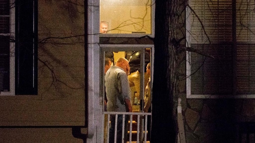 Police stand in the doorway of a home while investigating the shooting scene where authorities say five people are dead, including the gunman, in Douglasville, Ga. on Saturday, Feb. 7, 2015. Douglas County Sheriff's Lt. Glenn Daniel said authorities received an emergency call Saturday around 3 p.m. reporting a shooting in the housing development west of Atlanta. Daniel says the gunman shot six people before fatally shooting himself, and the two surviving victims are children, but children are also among the dead. (AP Photo/David Goldman)