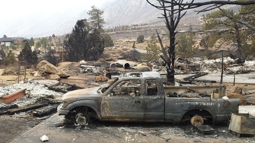 Vehicles are burned and homes are reduced to rubble in the community of Swall Meadows, Calif., Sunday, Feb. 8, 2015. Fire crews increased containment of a wind-driven wildfire that destroyed 40 homes, but they said Sunday that they still didn't know when residents evacuated from two small California towns at the eastern base of the Sierra Nevada would be able to return home. (AP Photo/Michelle Rindels)