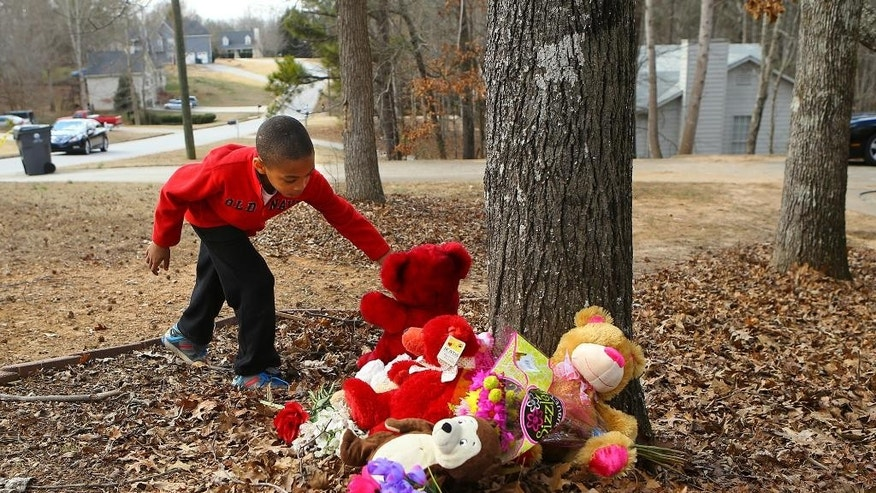 Feb. 8, 2015: Eight-year-old Emmanuel Cook leaves a red teddy bear at the scene of a domestic dispute the day after seven people were shot in Douglasville, Ga. (AP)