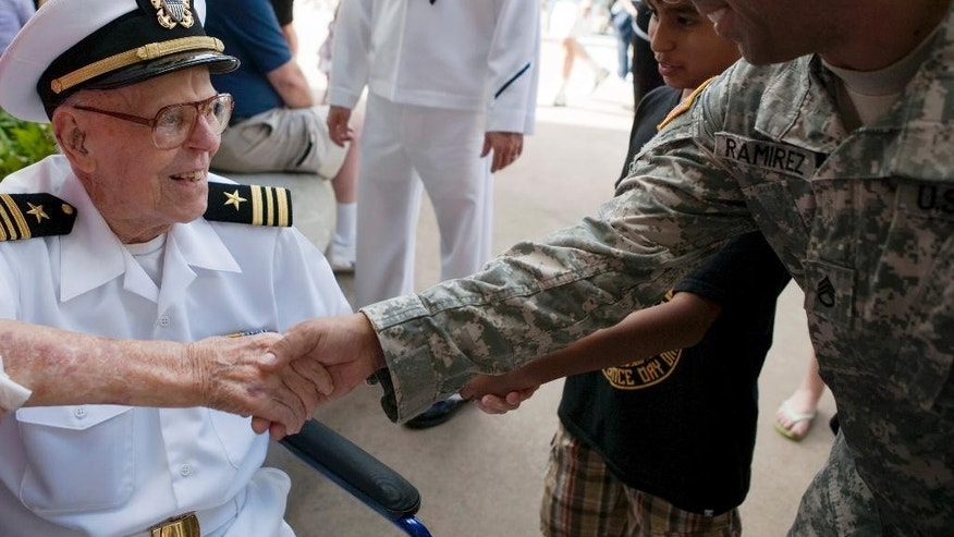 FILE - In a Wednesday, Dec. 7, 2011 file photo, USS Arizona survivor Joseph Langdell, left, greets Sgt. Carlos Ramirez at the Pearl Harbor Memorial, in Pearl Harbor, Hawaii.  Langdell, the oldest living crew member of the USS Arizona to have survived the Japanese attack on Pearl Harbor has died in Northern California at the age of 100. (AP Photo/Marco Garcia, File)