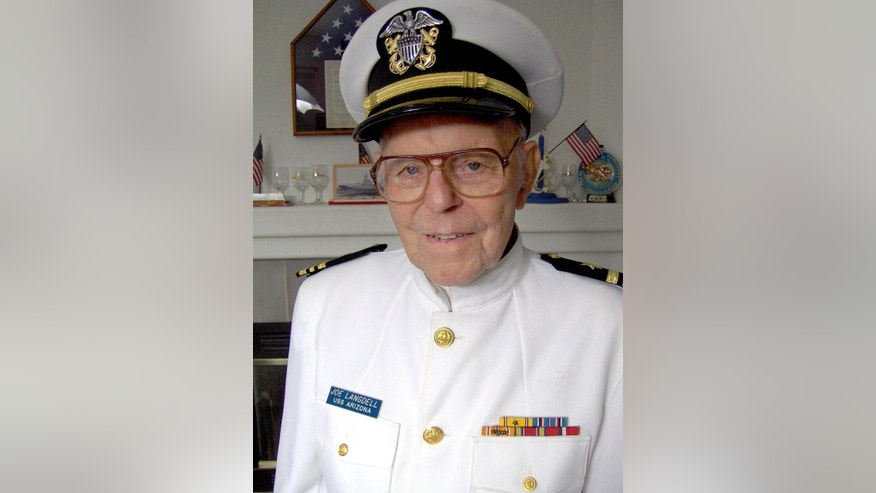 This Nov. 13, 2006 photo provided by Ted Langdell shows retired Navy Lt. Commander Joseph Langdell wearing his dress white uniform in front of the mantle of his former home in Yuba City, Calif. Langdell, the oldest living crew member of the battleship USS Arizona to have survived the Japanese attack on Pearl Harbor, has died on Feb. 4, 2015, in Northern California at the age of 100. (AP Photo/Ted Langdell)