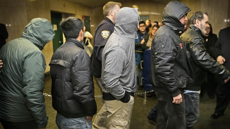 People chained together arrive for arraignment in a bribery scandal, Tuesday, Feb. 10, 2015, in New York. City inspectors, landlords and contractors formed a 50-person network that exchanged $450,000 in payoffs to get safety violations dismissed, procure phony eviction orders and get favorable and sometimes nonexistent inspections, authorities said Tuesday. (AP Photo/Seth Wenig)