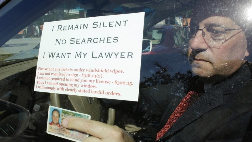 In this Friday, Jan. 30, 2015 photo, attorney Warren Redlich holds up a flyer he designed following an interview in Delray Beach, Fla. The DUI attorney contends that when a driver approaches a police drunk-driving checkpoint, they don't have to speak to the officers. He contends that commonly-used police drunk driving checkpoints violate drivers' constitutional rights. (AP Photo/Lynne Sladky)
