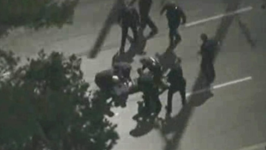 In this frame grab from aerial video provided by KABC-TV, authorities apprehend a gunman who led them on a wild chase east of Los Angeles, Monday, Feb. 9, 2015. The suspect smashed into cars, veered into oncoming traffic, stole a vehicle at gunpoint and ran down a crowded street before officers shot and wounded him. (AP Photo/KABC-TV)