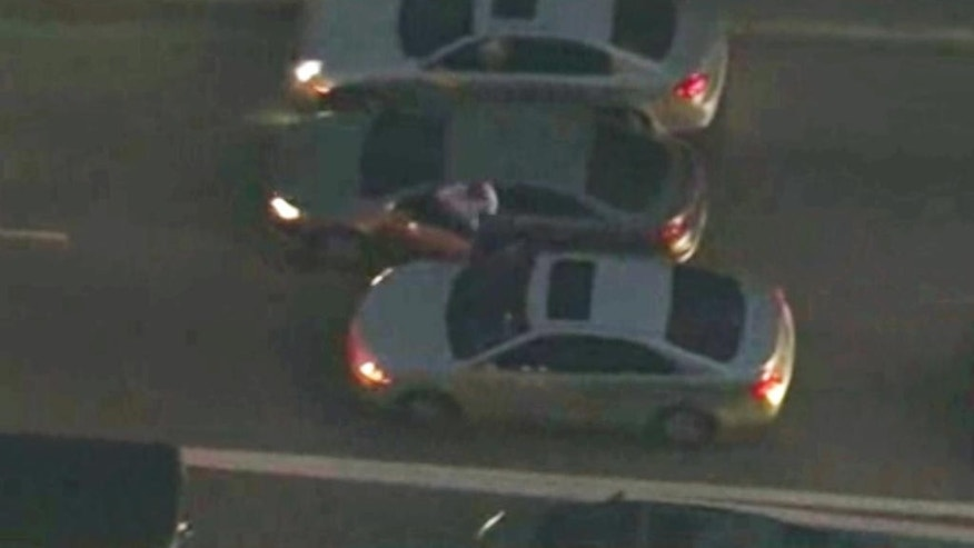 In this frame grab from aerial video provided by KABC-TV, a suspect gets out of a car during a chase east of Los Angeles, Monday, Feb. 9, 2015. The suspect smashed into cars, veered into oncoming traffic, stole a vehicle at gunpoint and ran down a crowded street before officers shot and wounded him. (AP Photo/KABC-TV)