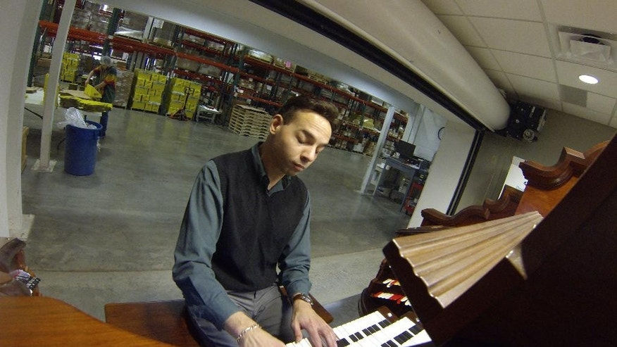 In this Jan. 26, 2015 photo, professional pipe organ player R. Jelani Eddington plays a theater pipe organ at Carma Laboratories. Inc warehouse in Franklin, Wis. The pipe organ if the personal passion of Carma Laboratories president Paul Woelbing who hired a Minneapolis-based company to build it in the company's Franklin warehouse with refurbished parts from around the country. (AP Photo/Carrie Antlfinger)