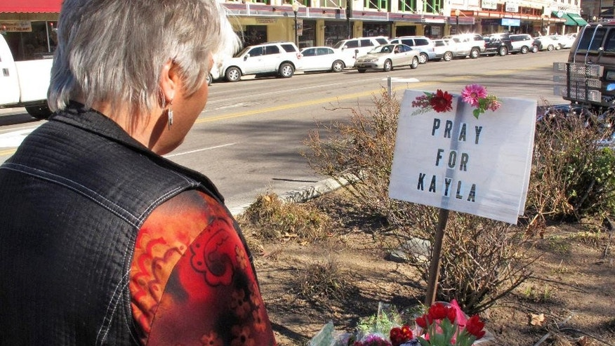 Laura Spaeth looks at a memorial honoring American hostage Kayla Mueller on the corner of courthouse plaza in Prescott, Ariz.,  Tuesday, Feb. 10, 2015.  Islamic State group reported Friday that Muller, whose 18-month captivity had largely been kept secret in an effort to save her, had died in a recent Jordanian airstrike targeting the militants. On Tuesday her parents and U.S. officials confirmed she was dead, although officials said they could not confirm how she died.  (AP Photo/Felicia Fonseca)