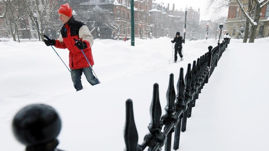 Massachusetts Department of Transportation assistant secretary Jeffrey Simon, left, and his wife Ginny Simon travel Monday, Feb. 9, 2015, along Newbury Street on cross-country skis in Boston. A long duration winter storm that began Saturday night remains in effect for a large swath of southern New England until the early morning hours Tuesday. (AP Photo/Steven Senne)