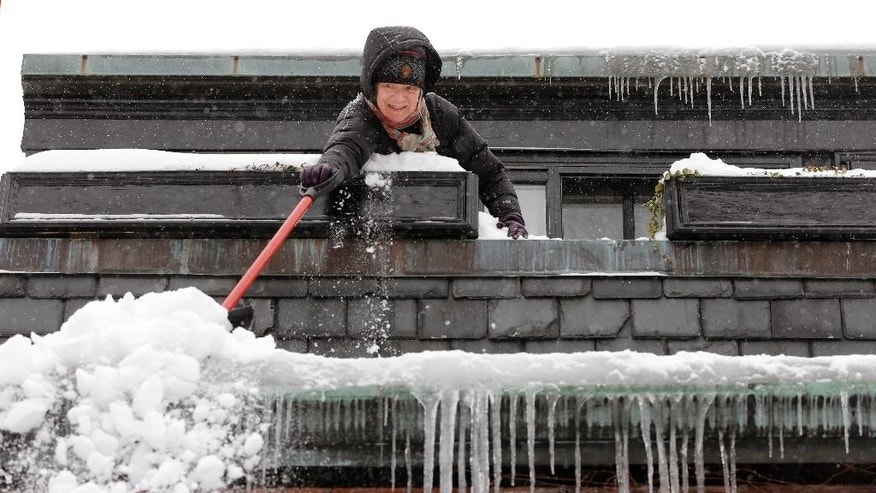 Susan Hartnett shovels snow from the roof of her Beacon Hill home Monday, Feb. 9, 2015, in Boston. A long duration winter storm that began Saturday night remains in effect for a large swath of southern New England until the early morning hours Tuesday. (AP Photo/Steven Senne)