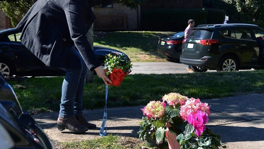 A woman places flowers at a makeshift memorial next to murder victim Deah Shaddy Barakat's car at the Finley Forest condominium complex Wednesday, Feb. 11, 2015 in Chapel Hill, NC . Craig Stephen Hicks, 46, of Chapel Hill, is accused of shooting Barakat, 23, Yusor Mohammad, 21, of Chapel Hill; and Razan Mohammad Abu-Salha, 19, of Raleigh, the day before. Hicks is being held in the Durham County jail with no bond.  (AP Photo/The News & Observer, Chuck Liddy)