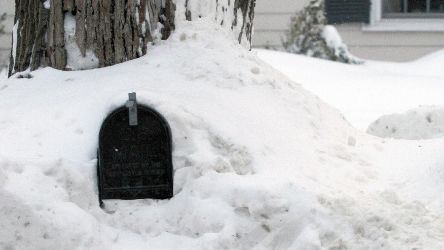 A mailbox sits in a pile of snow Wednesday, Feb. 11, 2015 in Weston, Mass. The National Weather forecasts a weak weather system that may bring 2 to 4 inches of new snow Thursday into Friday morning to the region, which already has seen record snowfalls this winter. (AP Photo/Bill Sikes)