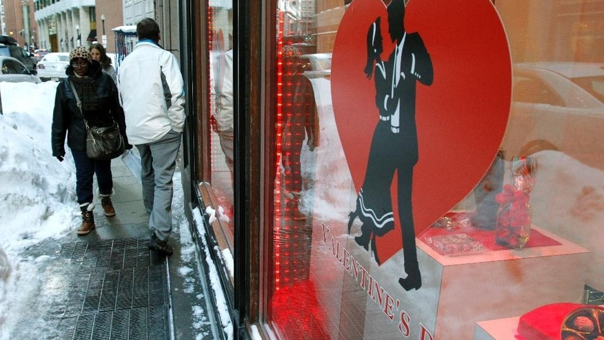 Commuters walk past piles of snow in front of Au Chocolat, Wednesday, Feb. 11, 2015, in downtown Boston. With streets boxed in by mountains of snow, delivery drivers in the region are struggling to deliver daily supplies to downtown stores, as well as Valentine's Day flowers and edibles. (AP Photo/Bill Sikes)