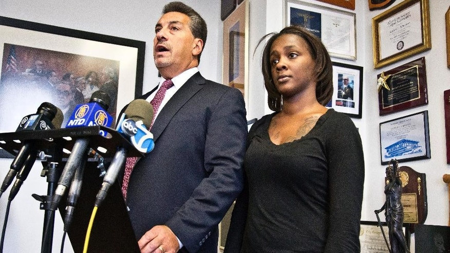 FILE - In this Jan. 29, 2015, file photo, Attorney Scott Rynecki, left, and Kimberly Ballinger, the domestic partner of Akai Gurley and mother of his daughter, hold a news conference in New York. Officer Peter Liang will appear in court Wednesday, Feb. 11, 2015, in the November shooting death of Gurley, according to Scott Rynecki, an attorney representing Gurley's family. Liang, who fired into a darkened stairwell at a Brooklyn public housing complex, accidentally killing Gurley who had been waiting for an elevator, has been indicted in his death, a lawyer said Tuesday. (AP Photo/Bebeto Matthews, File)