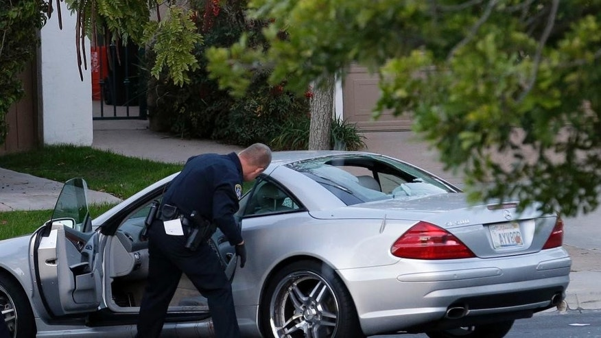 Police examine the scene following a shooting Tuesday, Feb. 10, 2015, in San Diego. CBS affiliate KFMB-TV says sports anchor Kyle Kraska was attacked Tuesday afternoon in the Scripps Ranch area of the city. (AP Photo/Gregory Bull)