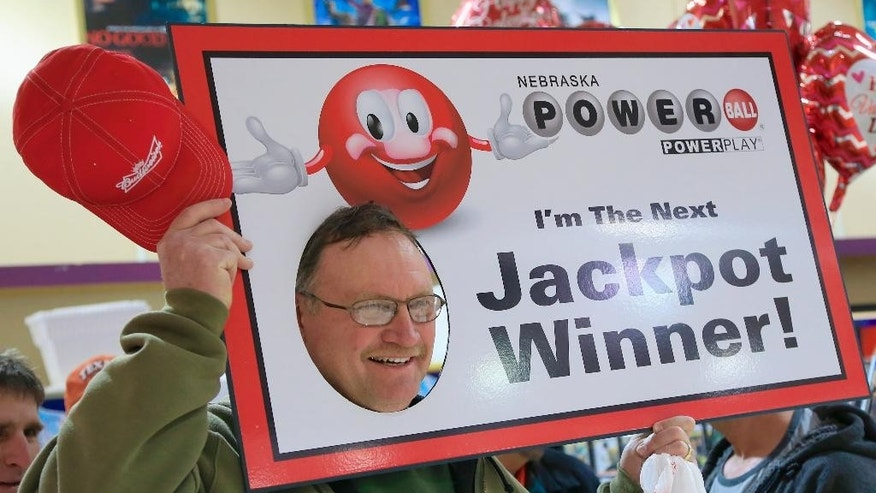 David Hanau, of Firth, Neb., poses with a sign as a lottery representative, unseen, takes his photo, at Russ's Market in Lincoln, Neb., where Powerball tickets were handed out for free as part of a promotion, Wednesday, Feb. 11, 2015. The Powerball jackpot has climbed to an estimated $500 million, which would make it the fifth largest lottery prize in U.S. history.