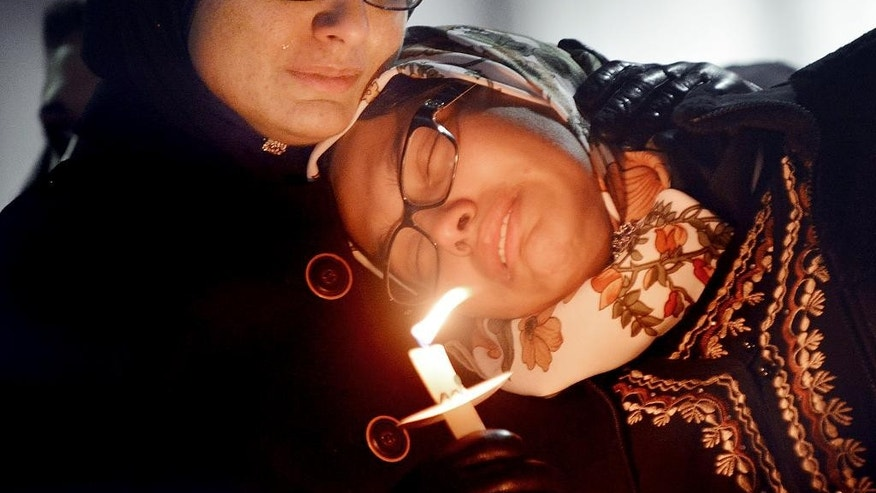 Women mourn during a vigil for three people who were killed at a condominium near UNC-Chapel Hill, Wednesday, Feb. 11, 2015, in Chapel Hill, N.C. Craig Stephen Hicks appeared in court Wednesday on charges of first-degree murder in the deaths Tuesday of Deah Shaddy Barakat, his wife Yusor Mohammad and her sister Razan Mohammad Abu-Salha. (AP Photo/The Herald-Sun, Bernard Thomas)