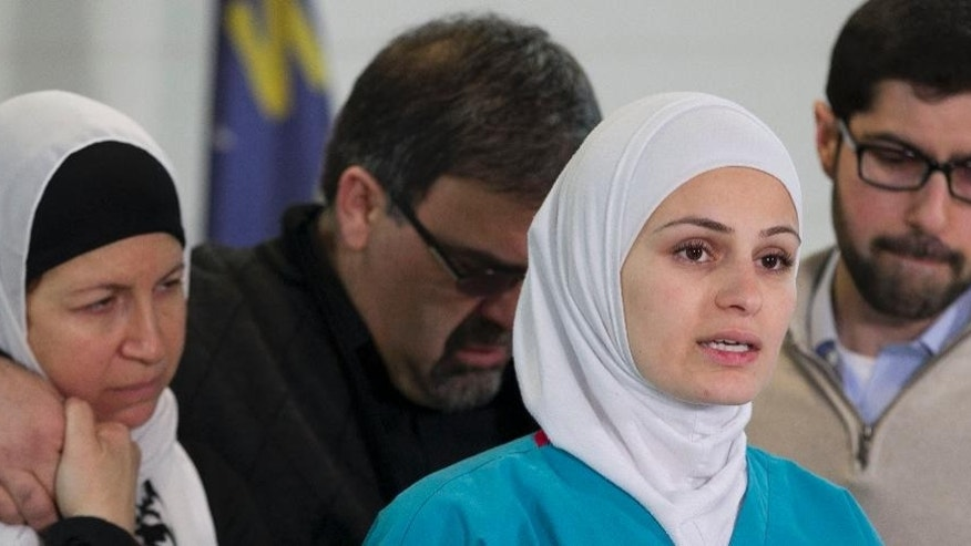 Suzann Barakat, front right, addresses members of the media on the death of her brother Deah Shaddy Barakat as her parents Namee and Layla Barakat, left, embrace behind her during a media availability in Raleigh, N.C., Wednesday, Feb. 11, 2015. Deah, his wife Yusor Mohammad and her sister Razan Mohanned Abu-Salha were killed in a triple homicide on Tuesday in Chapel Hill, N.C. (AP Photo/The News & Observer, Robert Willett) MANDATORY CREDIT