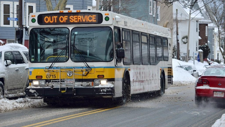 An out-of-service transit bus rolls through Somerville, Mass.,Tuesday, Feb. 10, 2015. The storm left the Boston-area with another two feet of snow and forced the MBTA to buses on a limited basis, and suspended all rail service for the day Tuesday to clean tracks and repair equipment. (AP Photo/Josh Reynolds)