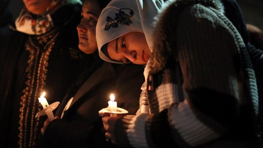 Suzanne Askar, right, rests her head on the shoulder of Safam Mahate, a student at North Carolina State University, as they stand next to Nida Allam, far left, during a vigil for three people who were killed at a condominium near UNC-Chapel Hill, Wednesday, Feb. 11, 2015, in Chapel Hill, N.C. Craig Stephen Hicks appeared in court on charges of first-degree murder in the Tuesday deaths of Deah Shaddy Barakat, his wife Yusor Mohammad and her sister Razan Mohammad Abu-Salha. (AP Photo/The News & Observer, Al Drago)