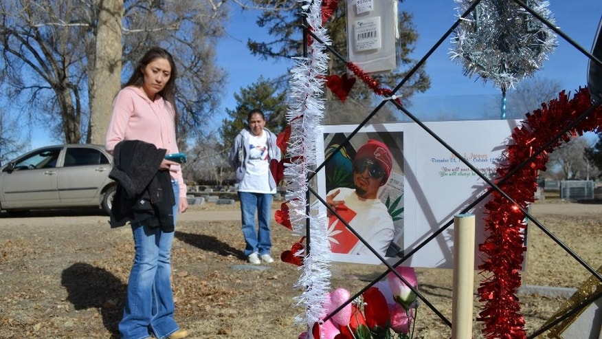 In this photograph taken on Thursday, Feb. 5, 2015, in Rocky Ford, Colo., Jackie Jacquez-Lindenmuth, front, looks over a memorial to her brother Jack Jacquez, who died after being shot by Rocky Ford, Colo., Police Department officer James Ashby on Oct. 12, 2014. Ashby faces second-degree murder charges, the first officer in more than 20 years to be charged with murder for an on-duty shooting in Colorado. Jackie's mother, Viola Jacquez, back, looks on at the memorial for her son, Jack. (AP Photo/P. Solomon Banda)
