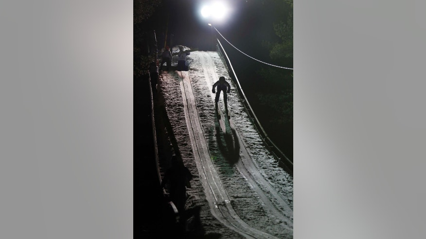 In this photo taken Wednesday Feb. 4, 2015 a high school ski jumper skis down the inrun as he competes in Newport, N.H. The state is the only place in the nation that still offers ski jumping as a competitive sport for high-schoolers. (AP Photo/Jim Cole)