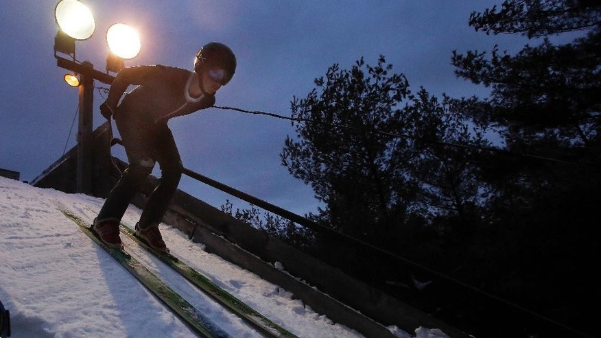 In this photo taken Wednesday Feb. 4, 2015 a high school ski jumper takes off in the darkness as he competes in Newport, N.H. The state is the only place in the nation that still offers ski jumping as a competitive sport for high-schoolers.(AP Photo/Jim Cole)