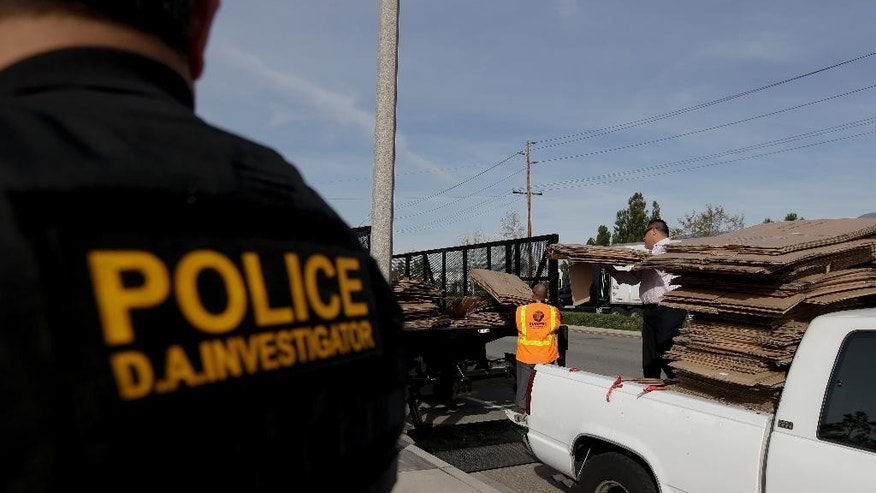 Steve Rivera, senior investigator with the San Bernardino County District Attorney office, left, watches as a load of cardboard is seized temporarily on Wednesday, Jan. 28, 2015 in Fontana, Calif. The load was found to be legitimately given to the driver the by a local furniture store owner on the premise they'd split the recycling proceeds. When the economy booms, cardboard prices rise as manufacturers make more goods and need more packaging to sell them. Thieves are more brazen, and steal much more, when cardboard prices peak. (AP Photo/Chris Carlson)