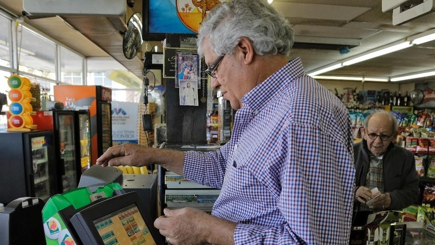 Farouk Tawfik sells Powerball lottery tickets at the Time Saver Food Mart Wednesday, Feb. 11, 2015, in Tampa, Fla. The Powerball jackpot has climbed to $500 million, making Wednesday night's drawing the fifth largest prize in U.S. history. (AP Photo/Chris O'Meara)